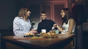 The boy and two girls are drinking tea. The young man and two young girls sitting in the evening in the kitchen and drink tea stock footage