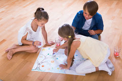 Boy and two girls playing at board game indoors. Boy and two little girls playing at board game indoors Stock Photos