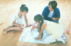 Boy and two girls playing at board game indoors Stock Photography