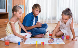 Boy and two girls playing at board game indoors. Boy and two little american girls playing at board game indoors Stock Photos