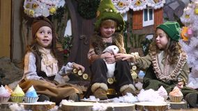 Funny children are sitting in a room with Christmas decorations and stroking a fluffy rabbit. A boy and two girls in sarin Christmas clothes are sitting in a stock video