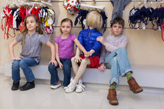 The boy and two girls sitting together with mannequins. In the store childrens clothes stock photography