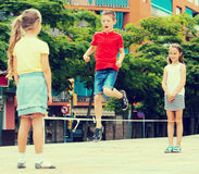 boy and two girls skipping on elastic jumping rope Royalty Free Stock Photography