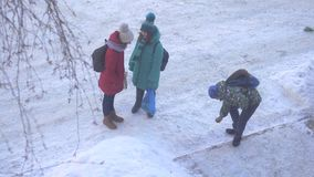 Boy and two girls talking in winter. A boy and two girls talking on the street in winter stock video