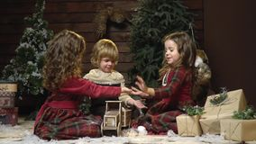 Three small children sit among the gifts and clap their hands, slow motion. A boy and two sisters are cute playing sitting amidst the Christmas decorations in a stock video footage