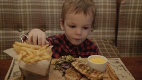 Boy of two years is eating french fries in a restaurant. Boy of two years is eating french fries in a restaurant stock video footage