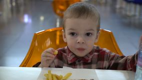 Boy of two years is eating French fries and waving his hand at the camera. Footage boy of two years is eating French fries and waving his hand at the camera stock video footage