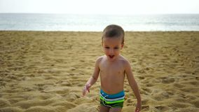 Boy of two years playing on the beach near the ocean. Boy of two years playing on the beach near the ocean stock video