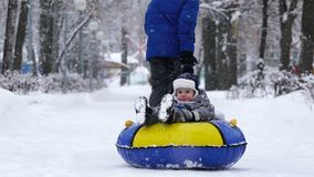 Boy of two years rolling on tubing in the park in winter. Boy of two years rolling on tubing in the park in winter stock footage
