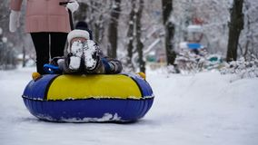 Boy of two years rolling on tubing in the park in winter. Boy of two years rolling on tubing in the park in winter stock video footage