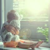 Boy of two years sitting by the window and hugs a toy Bunny. rainy weather, waiting for dad to come home from work royalty free stock photography