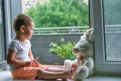 Boy of two years sitting by the window and hugs a toy Bunny. rainy weather, waiting for dad to come home from work royalty free stock photos