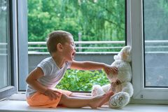 Boy of two years sitting by the window and hugs a toy Bunny. rainy weather, waiting for dad to come home from work stock photos