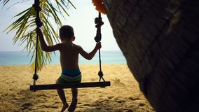 Boy of two years swings on a swing on the beach near the ocean. Boy of two years swings on a swing on the beach near the ocean stock video footage