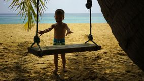 Boy of two years swings on a swing on the beach near the ocean. Boy of two years swings on a swing on the beach near the ocean stock footage