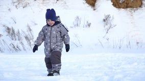 Boy of two years walks in winter. stock video