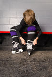 Boy Tying Hockey Skates in Dressing Room Royalty Free Stock Photography