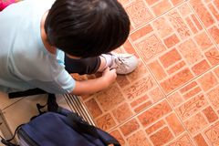 A boy is tying the shoelaces to prepare to go to school in the m. Orning at home hastily. Copy space for words Stock Image