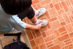 A boy is tying the shoelaces to prepare to go to school in the m. Orning at home hastily. Copy space for words Royalty Free Stock Photo