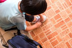 A boy is tying the shoelaces to prepare to go to school in the m. Orning at home hastily. Copy space for words Royalty Free Stock Photos