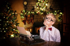 Boy typing a letter to Santa Claus on the typewriter Royalty Free Stock Image