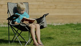 Boy typing on phone. Blond boy typing on smartphone and smiling sitting outside in a yard stock video footage