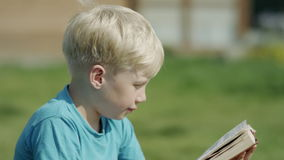 Boy typing on phone. Blond boy typing on smartphone and smiling sitting outside in a yard stock video