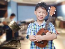 Boy with ukulele at music school stock images