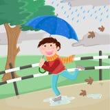 Boy with umbrella. Running happily in the rain Stock Photo