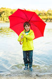Boy with umbrella. Joyful boy with umbrella hopping in water Stock Photo