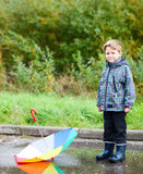 Boy with umbrella in puddle Stock Photography