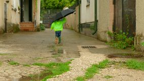 Boy with an umbrella running around the yard in rubber boots. The boy with an umbrella after the rain running through the yard. the legs of the boy are shod in stock footage