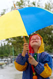 The boy with an umbrella standing under a rain Royalty Free Stock Images