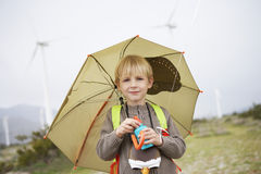 Boy With Umbrella At Wind Farm Royalty Free Stock Photography