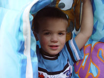 Boy Under Blanket. Three year old boy holding up blanket royalty free stock photo