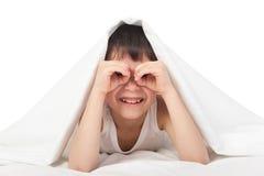 Boy under blanket look through his palms like binoculars Stock Photo