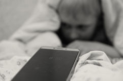 The boy at 8.30 am from under the blankets does not want to wake up to school. Stock Photo