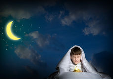 Boy under the covers with a flashlight Royalty Free Stock Photos