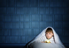 Boy under the covers with a flashlight Stock Photos