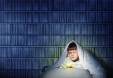 Boy under the covers with a flashlight Royalty Free Stock Photography