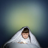 Boy under the covers with a flashlight Stock Images