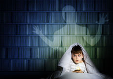 Boy under the covers with a flashlight Stock Photo