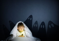Boy under the covers with a flashlight Royalty Free Stock Images