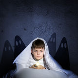 Boy under the covers with a flashlight Stock Photography