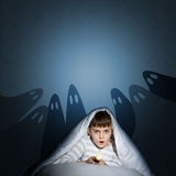 Boy under the covers with a flashlight Royalty Free Stock Photo