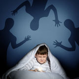 Boy under the covers with a flashlight Royalty Free Stock Image