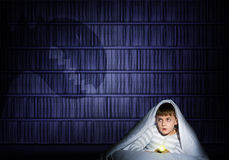 Boy under the covers with a flashlight Stock Image