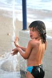 The boy under a shower. The boy plays about with water under a beach shower on the sea Stock Photo