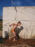 Boy under shower. Boy under cold shower at the beach Royalty Free Stock Image