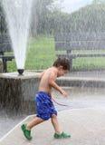 Boy under sprinkler Royalty Free Stock Images